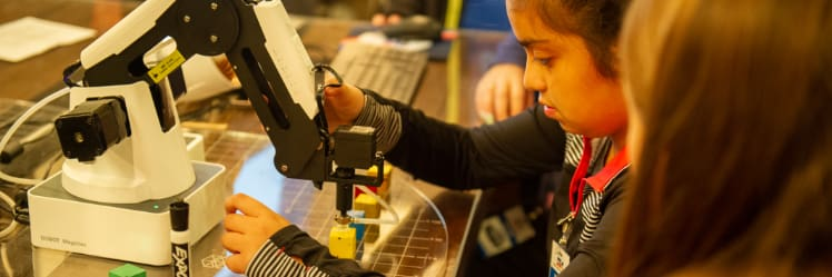 Elementary school students learn to execute tasks with a robotic arm much like those found in advanced manufacturing facilities.