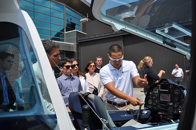 Flight instructor Kirk Choquette shows members of the Ricci Family Foundation the features of a Sky Arrow L600 sport plane.