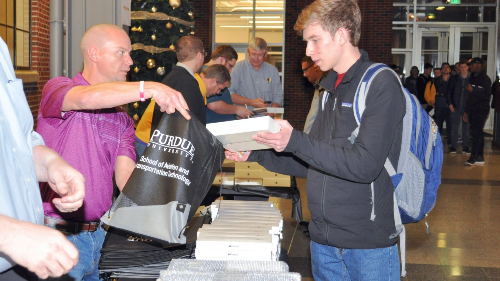 Purdue staff members distribute new Electronic Purdue Bags, each with iPad, Apple Pencil & Logitech keyboards, to students in the School of Aviation and Transportation Technology