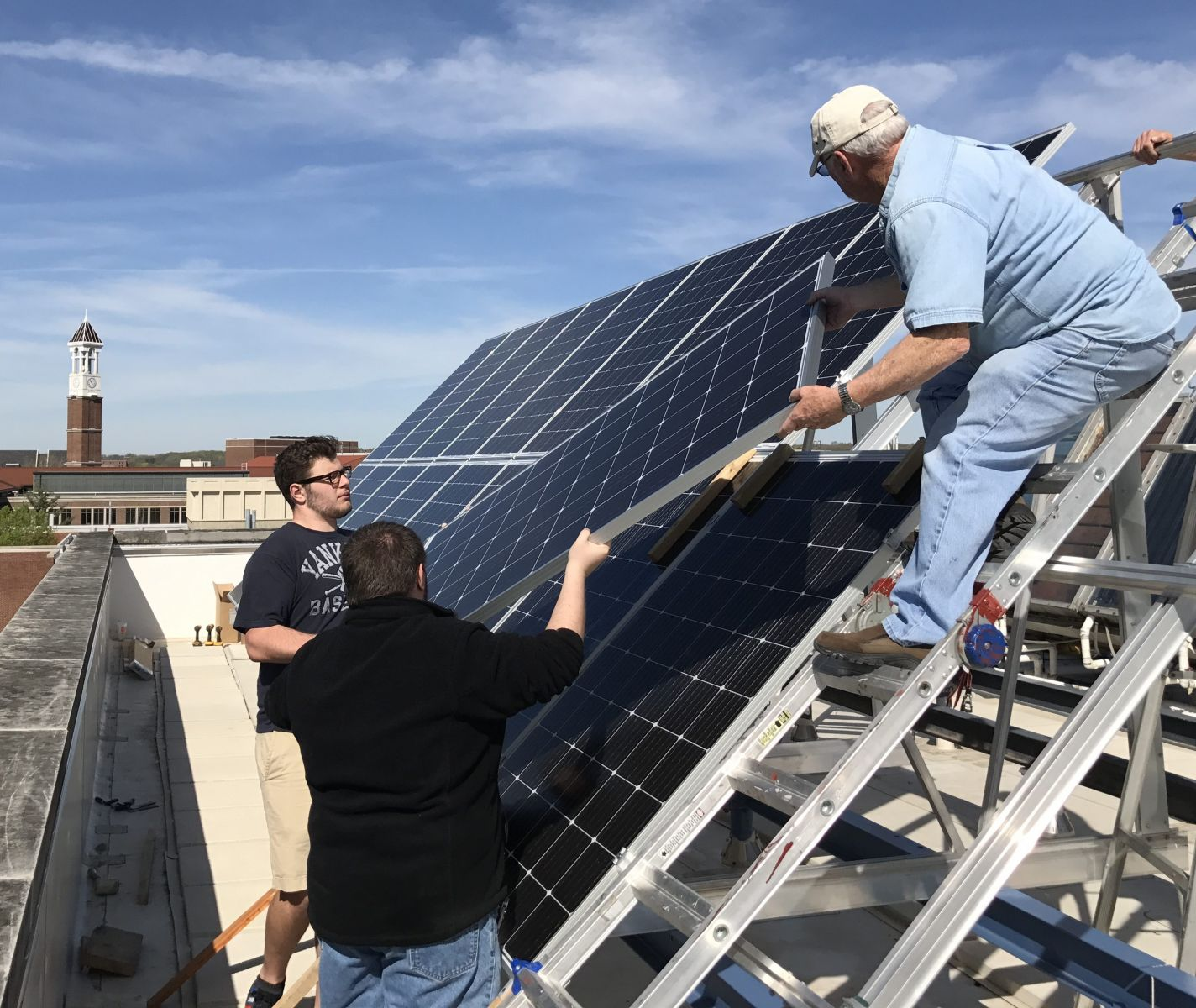 Students hand off a new solar panel on Knoy's rooftop