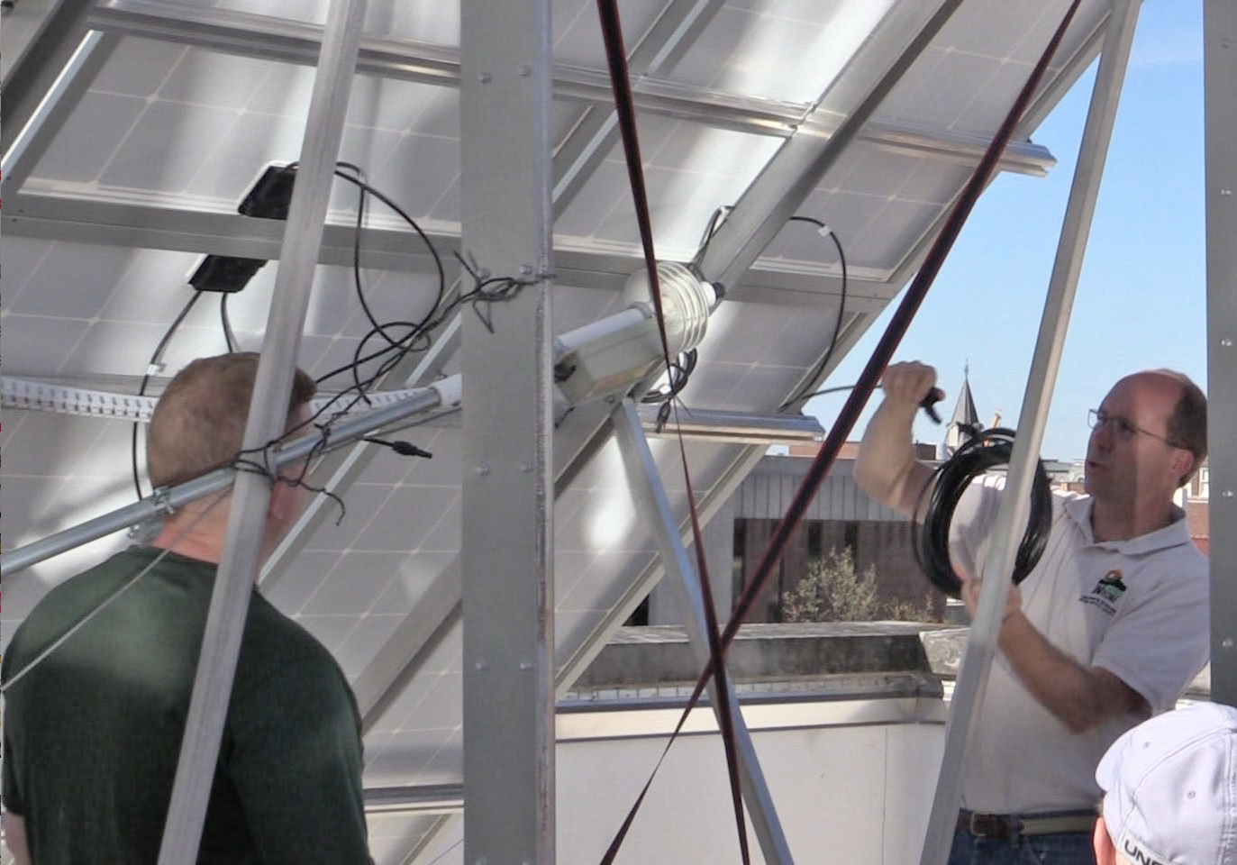 Bill Hutzel (right) discusses the new array's plug-and-play electrical connections with the installation team