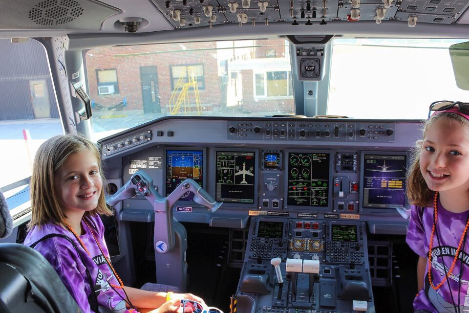Girls sit in the cockpit a jet at the Purdue Airport during the 2017 Girls in Aviation Day