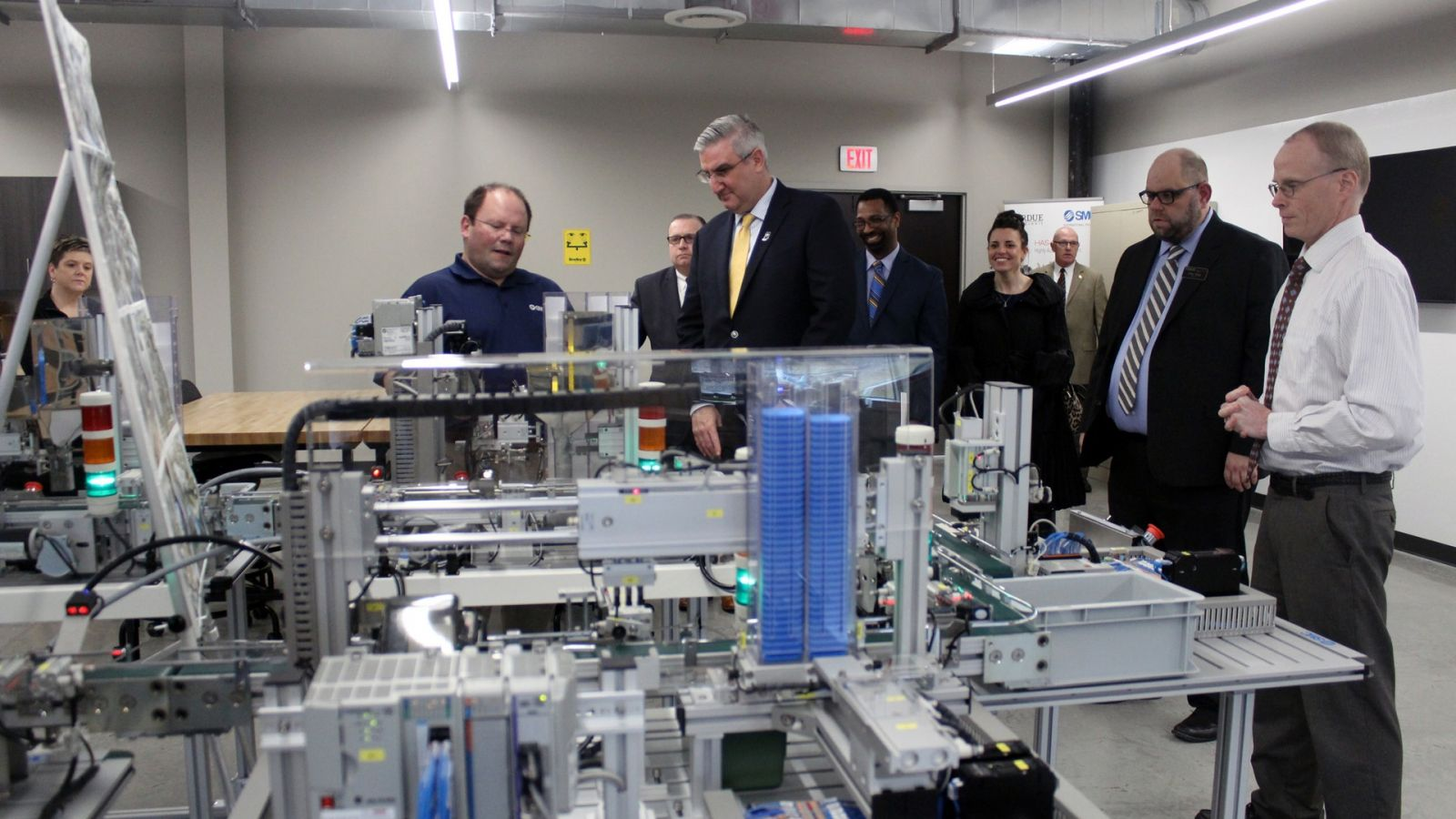 Indiana Governor Holcomb (center) talks with John Wardwell (left), national training manager at SMC Corporation, Corey Sharp (second from right), director of Purdue Polytechnic Anderson, and John Halverson (far right), director of marketing at SMC Corporation, about the SMC HAS 200, a key training system for mechatronics engineering technology students. (Photo courtesy Office of Gov. Holcomb)