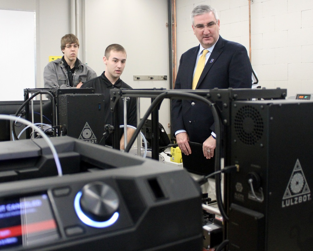 Dylan Alkire and Lucas Gibbons, Purdue Polytechnic engineering technology students, share with Gov. Holcomb how they use 3-D printing technology for design, prototyping, materials and processes courses at the Anderson location. (photo courtesy Office of Gov. Holcomb)
