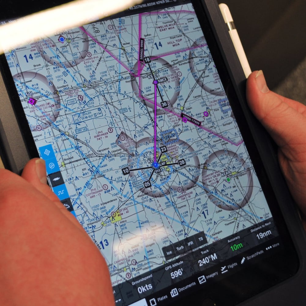 The Electronic Purdue Bag's iPad screen displaying a VFR (Visual Flight Rules) Sectional Chart. The pink line indicates the direct course between airports. The app also allows users to overlay weather conditions and other data.