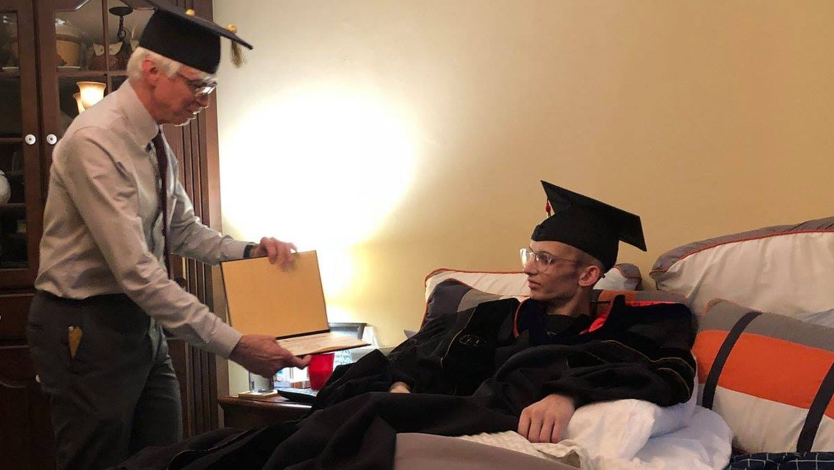 Gary Bertoline, dean of Purdue Polytechnic, awards an Associate of Science Degree to Tyler Trent.