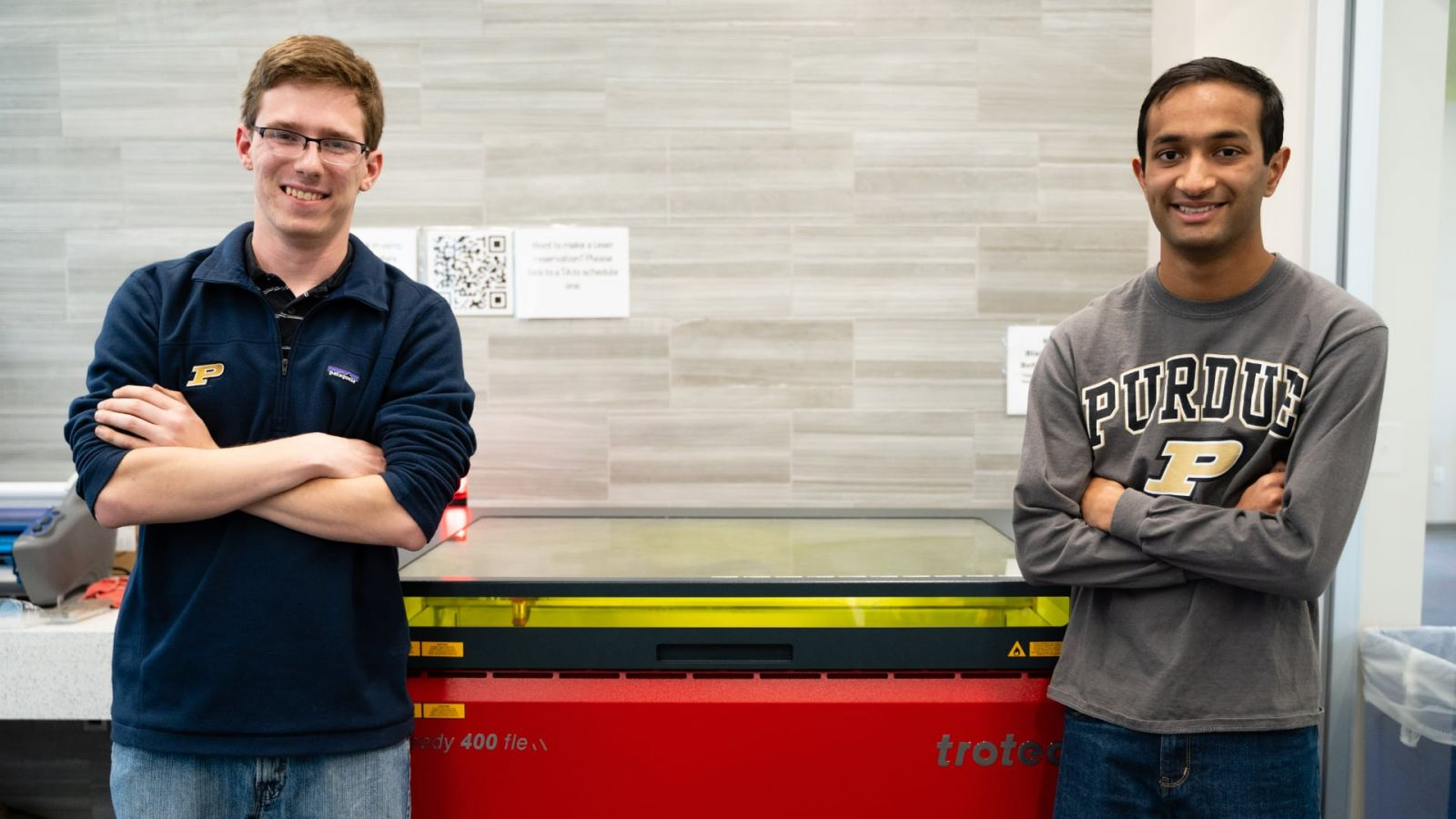 Purdue University students Matthew Fitzgerald and Shiv Patel stand before a laser engraver at the Bechtel Innovation Design Center. The students engraved 36 bookends to commemorate the historic Lafayette Street Railway. (Nick Wang/Purdue Foundry)