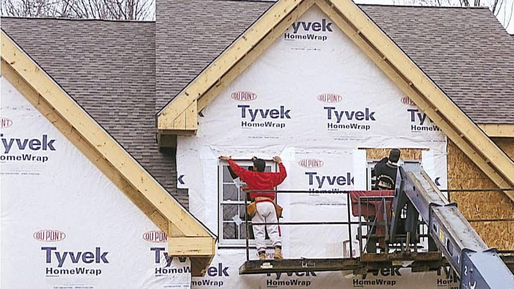 A version of Tyvek, the synthetic, waterproof material shown here on a home under construction, can be made into isolation gowns.