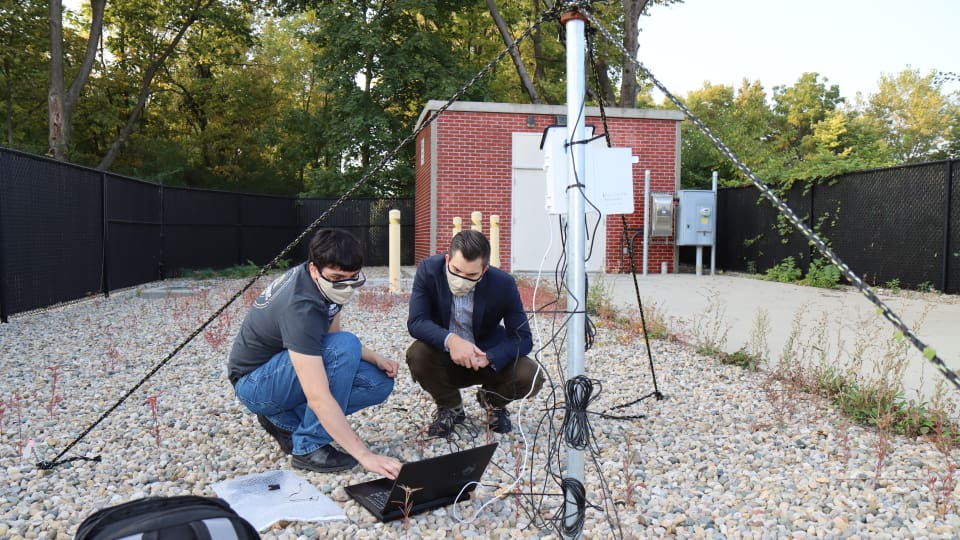 Luis Maldonado and Jason Ostanek check weather sensor data at a cellular transmitter adjacent to ventilation shafts connected to Citizens Energy Group's DigIndy Tunnel System in Indianapolis, Indiana. (Purdue University photo/John O'Malley)