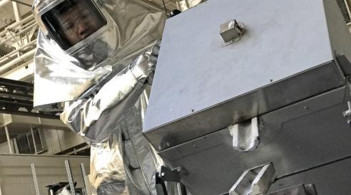 Xingtao Liu demonstrates how he would use a furnace to pour molten aluminum.